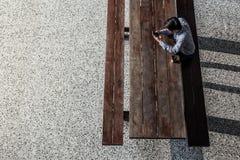 Młody Człowiek sitiing Pracować na Smartphone w szkole wyższa Odgórny widok obraz royalty free