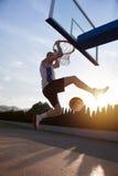 Młody człowiek skacze fantastycznego trzaska wsad bawić się stree i robi Zdjęcia Stock