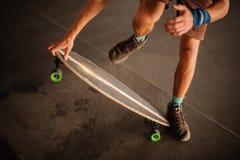 Młody człowiek skacze na longboard w brown sneakers zdjęcie royalty free