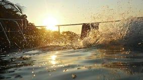 Młody człowiek skacze tylnego trzepnięcie w basen wodzie przy zmierzchem przez słońca i wody chełbotania z pięknym bokeh zdjęcie wideo