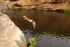 Młody człowiek skacze w rzekę Fotografia Royalty Free