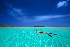 Młody człowiek snorkeling w tropikalnej lagunie z nadmiernymi wodnymi bungalowami Fotografia Royalty Free