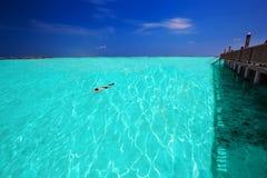 Młody człowiek snorkeling w tropikalnej lagunie z nadmiernymi wodnymi bungalowami Obraz Stock