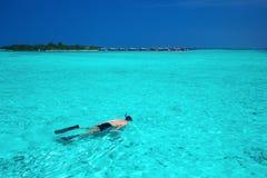 Młody człowiek snorkeling w tropikalnej lagunie z nadmiernymi wodnymi bungalowami Obrazy Royalty Free