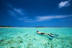 Młody człowiek snorkling w tropikalnej lagunie z nadmiernymi wodnymi bungalowami Fotografia Royalty Free