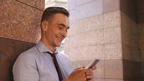 Młody człowiek sprawdza jego telefon pozycję na ulicie zbiory