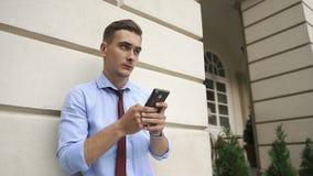 Młody człowiek sprawdza jego telefon pozycję na ulicie zdjęcie wideo