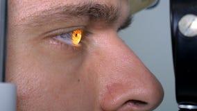 Młody człowiek sprawdza oczy na nowożytnym wyposażeniu w centrum medycznym zdjęcia stock