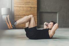 Młody człowiek sprawności fizycznej trening, siedzi chrupnięcia dla abs zdjęcia royalty free