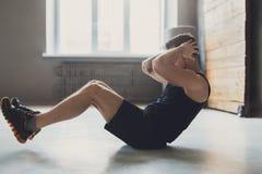 Młody człowiek sprawności fizycznej trening, siedzi chrupnięcia dla abs obraz stock