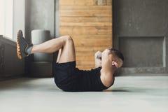 Młody człowiek sprawności fizycznej trening, siedzi chrupnięcia dla abs obraz royalty free