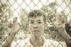 młody człowiek stali lub metalu klatkowa behind sieć Obrazy Stock