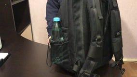 Młody człowiek stawia bidon w jego plecaku, przymocowywa jego kurtkę na jego klatce piersiowej i opuszcza, zbiory