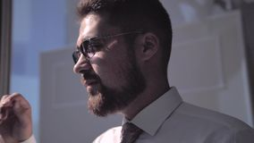 Młody człowiek stawia dalej jego szkła i stylishly przystosowywa one zbiory wideo