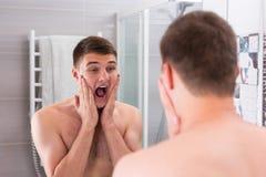 Młody człowiek stawia niektóre aftershave płukankę na twarzy dwa rękami i Zdjęcie Stock