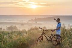 Młody człowiek stoi blisko bicyklu w ranku wschodzie słońca z wonderf Zdjęcia Royalty Free