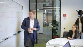 Młody człowiek stoi blisko magnesowego whiteboard i opowiada kolega w firmie zbiory