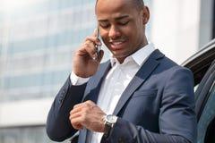 Młody człowiek stoi blisko samochodu opowiada na smartphone szczęśliwym sprawdza czasie na zegarku w górę obraz royalty free