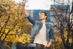 Młody człowiek stoi outdoors trzymać telefon komórkowego Obrazy Stock