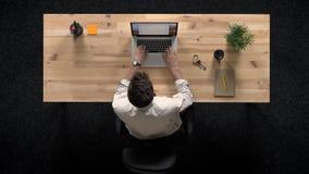 Młody człowiek stuka na laptopie, obraca daleko komputer, pracy pojęcie, biurowy pojęcie, komunikacyjny pojęcie, odgórny strzał zbiory wideo