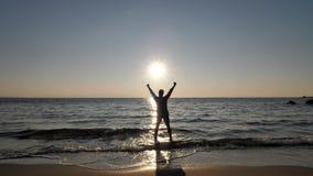 Młody człowiek sylwetka biega morze i podnosi up ręki, wdzięczne dla wschodu słońca, zwolnione tempo zdjęcie wideo