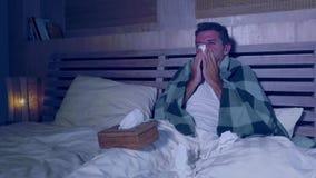 Młody człowiek sypialni cierpienia grippe uczucie cierpiący, chory kichnięcie i podmuchowy nos zakrywający z koc w zimy zimnie w  zbiory wideo