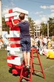 Młody człowiek sztuki jenga gigantyczna gra outdoors używa drabinę zdjęcie stock