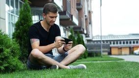 Młody człowiek sztuki mobilna gra na smartphone, siedzi na trawie blisko budynku zbiory