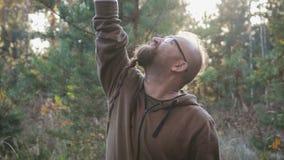 Młody człowiek szuka telefonu komórkowego sygnał w drewnach z brodą zbiory