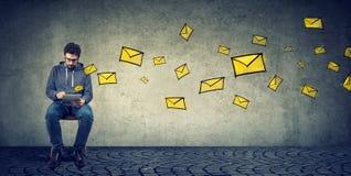 Młody człowiek texting na pastylki dosłania emailach podczas gdy pozujący na szarość Obraz Stock