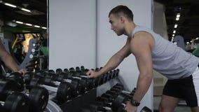 Młody człowiek trenuje z dumbbells klubem sportowym indoors zdjęcie wideo