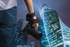 Młody człowiek trzyma czarną nowożytną cyfrową kamerę obraz royalty free