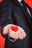 Młody człowiek trzyma czerwonego serce na palmie Zdjęcia Stock