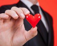 Młody człowiek trzyma czerwonego serce na palmie Zdjęcie Royalty Free
