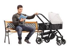Młody człowiek trzyma czytelniczej książki i wózka spacerowego Obraz Royalty Free