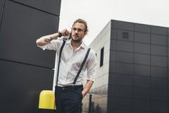 Młody człowiek trzyma gazetę i odprowadzenie z ręką w kieszeni w eyeglasses Zdjęcia Stock