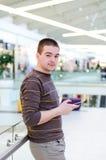 Młody człowiek trzyma jego smarthphone w miastowym tle Fotografia Royalty Free