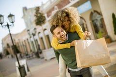 Młody człowiek trzyma młodej kobiety na jego z powrotem, zabawę i iść sho, zdjęcia stock