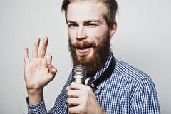 Młody człowiek trzyma mikrofon Obrazy Stock