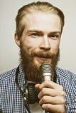 Młody człowiek trzyma mikrofon Fotografia Stock