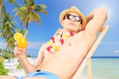 Młody człowiek trzyma obsiadanie na słońca lounger i koktajl Zdjęcie Stock