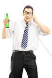 Młody człowiek trzyma piwo i opowiada na telefonie Obraz Stock