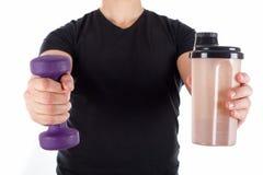 Młody człowiek trzyma proteinowego potrząśnięcie i dumbbell Obraz Stock