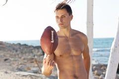 Młody człowiek trzyma rugby piłkę Obrazy Royalty Free