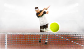 Młody człowiek trzyma tenisowego kant i piłkę podczas gdy trenujący Zdjęcie Royalty Free