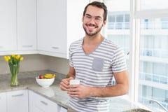 Młody człowiek uśmiecha się kawę i trzyma Zdjęcia Royalty Free