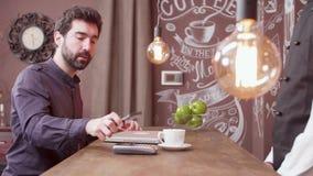 Młody człowiek używa jego smartphone robić zapłacie przy prętowym kontuarem i liśćmi zdjęcie wideo