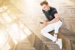 Młody człowiek używa jego smartphone z hełmofonami, słucha muzykę zdjęcie stock
