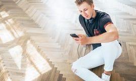 Młody człowiek używa jego smartphone z hełmofonami, słucha muzykę obrazy royalty free