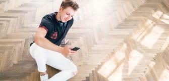 Młody człowiek używa jego smartphone z hełmofonami, słucha muzykę obrazy stock